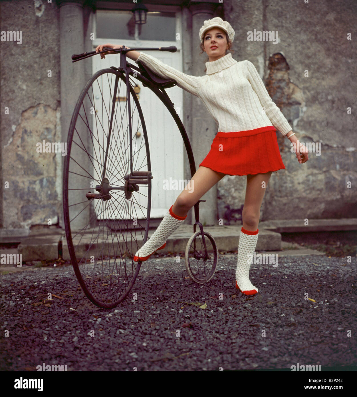 Model Anna Andreucetti wearing a Cyril Cullen creation Clothing Fashion Jumper Hat Skirt Boots Transport Bicycle - Stock Image