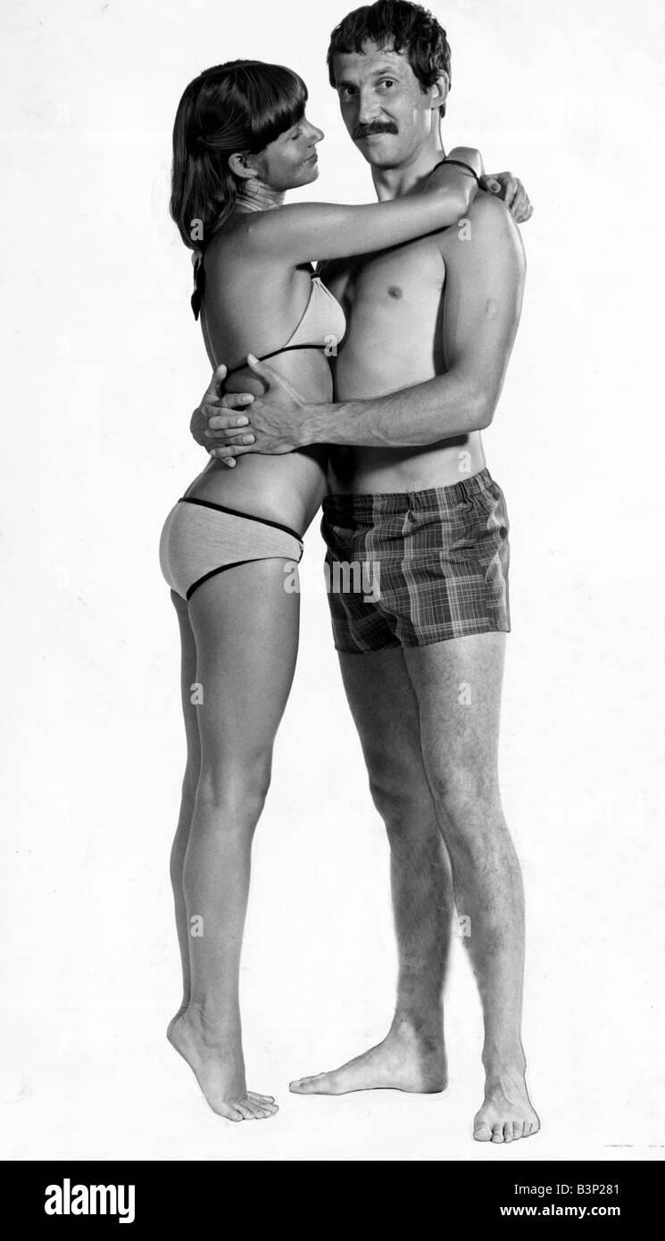 A man wearing checked shorts embracing a woman wearing a bikini August 1976 fashion male female swimwear beach men - Stock Image