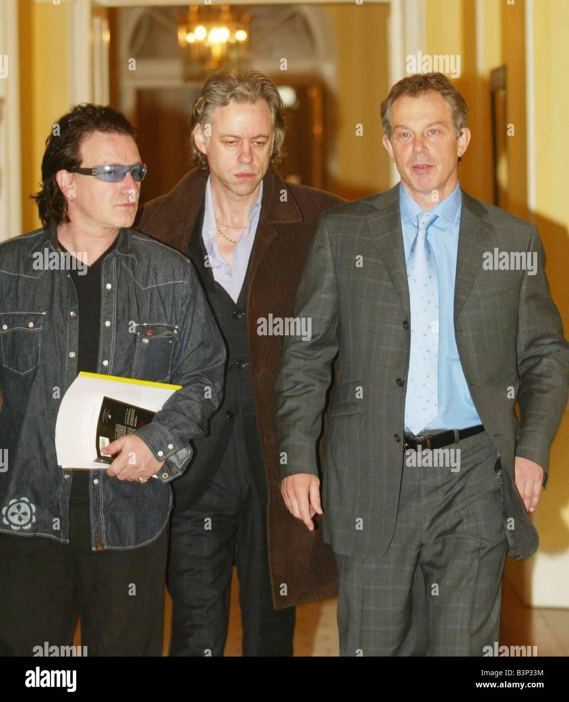Britain s Prime Minister Tony Blair May 2003 right escorts Sir Bob Geldof center and U2 frontman Bono inside 10 - Stock Image