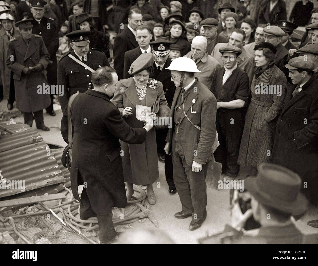 King George VI and Queen Elizabeth visit the East End London during WW2 1939 1945 A serviceman shows a picture of - Stock Image