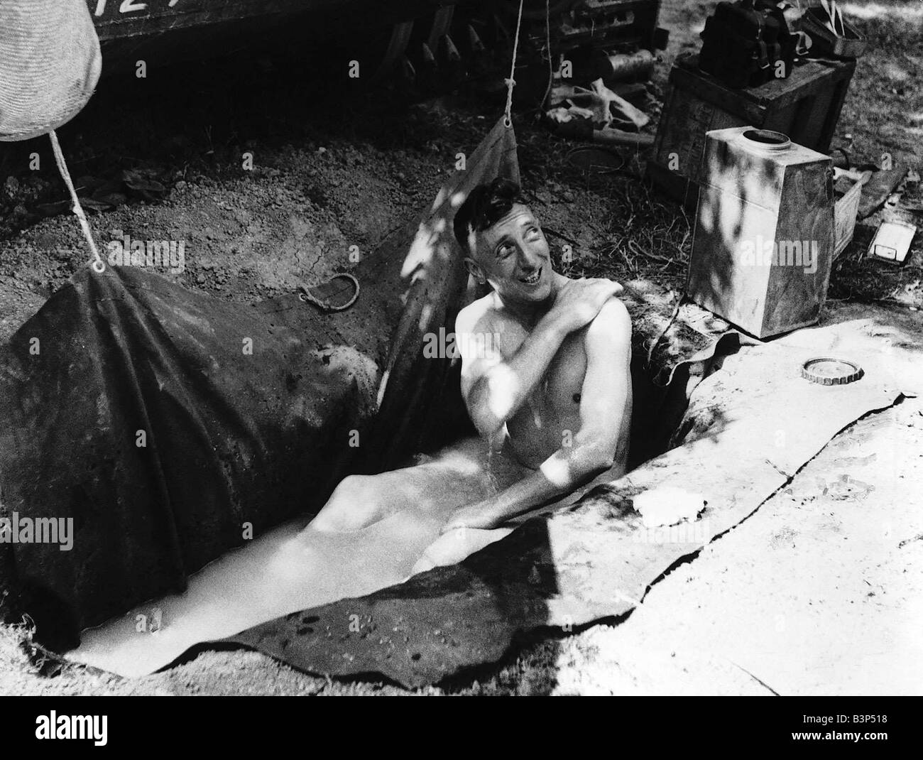 WW2 Corporal W Noble of Northampton taking a bath in a groundsheet placed in a slit trench before going into action - Stock Image