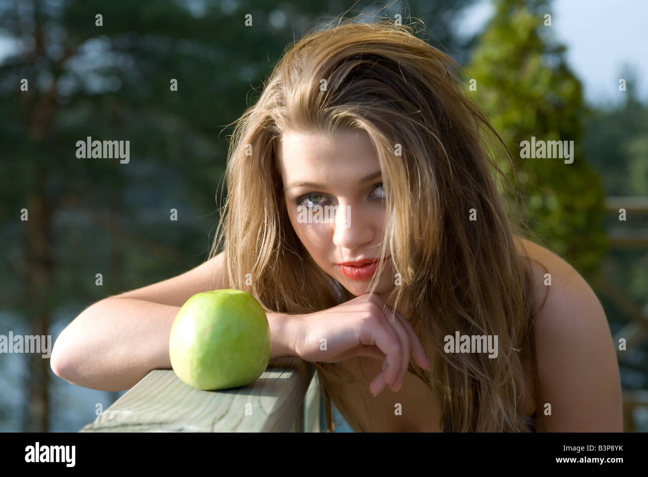Girl with apple on sunset - Stock Image