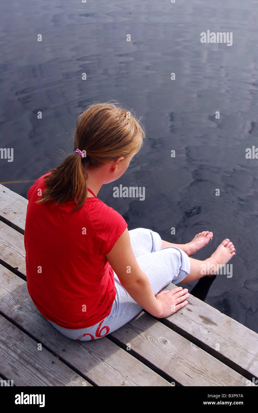 Young girl sitting on the edge of boat dock dipping her feet in water -  Stock