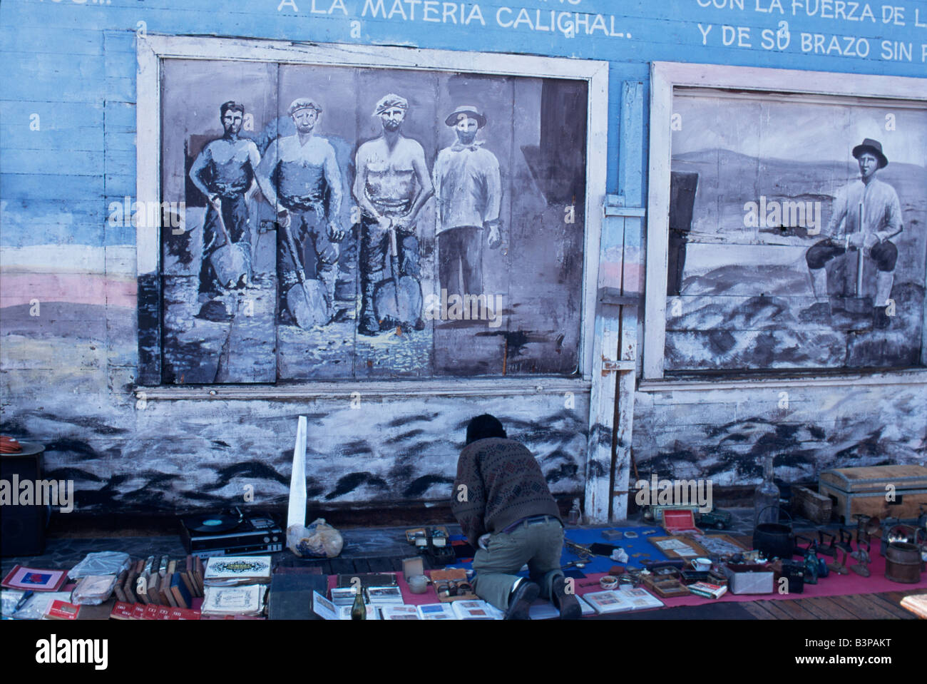 Chile, Region 1, Iquique. A street trader lays out his wares, artefacts from the nineteenth century nitrate boom, - Stock Image
