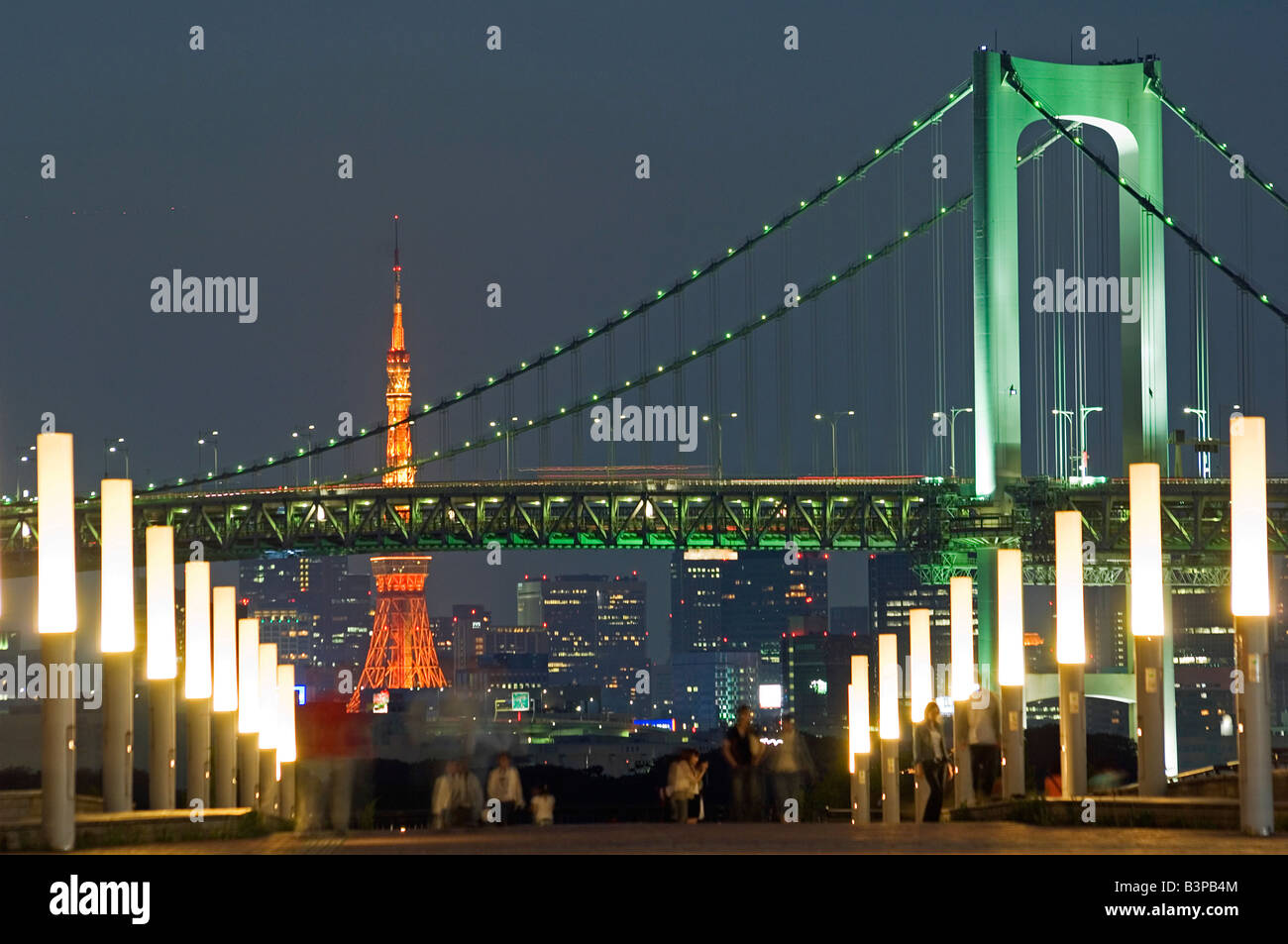 Japan, Tokyo, Odaiba . Rainbow Bridge and Tokyo Tower, people in the foreground taking an evening stroll. - Stock Image