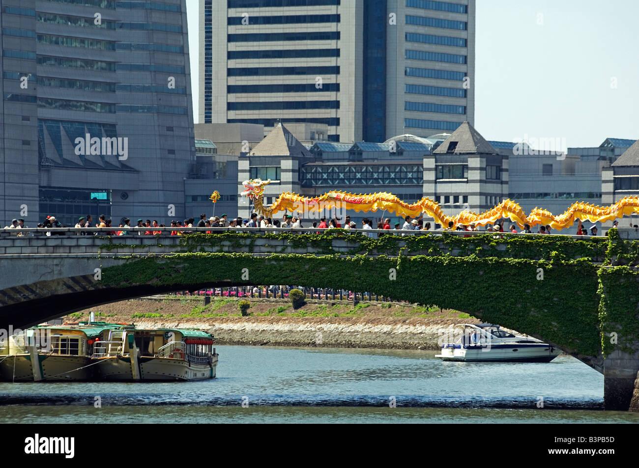 Japan, Kanagawa prefecture, Yokohama. Chinese Dragon dancers crossing the city bridge during the International parade. - Stock Image