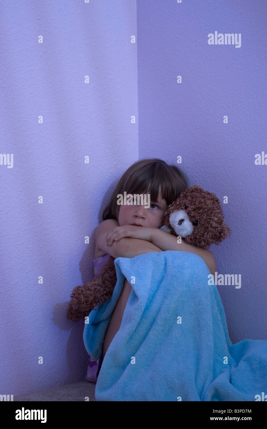 Frightened young girl sitting in a corner hugging her blanket and teddy bear - Stock Image