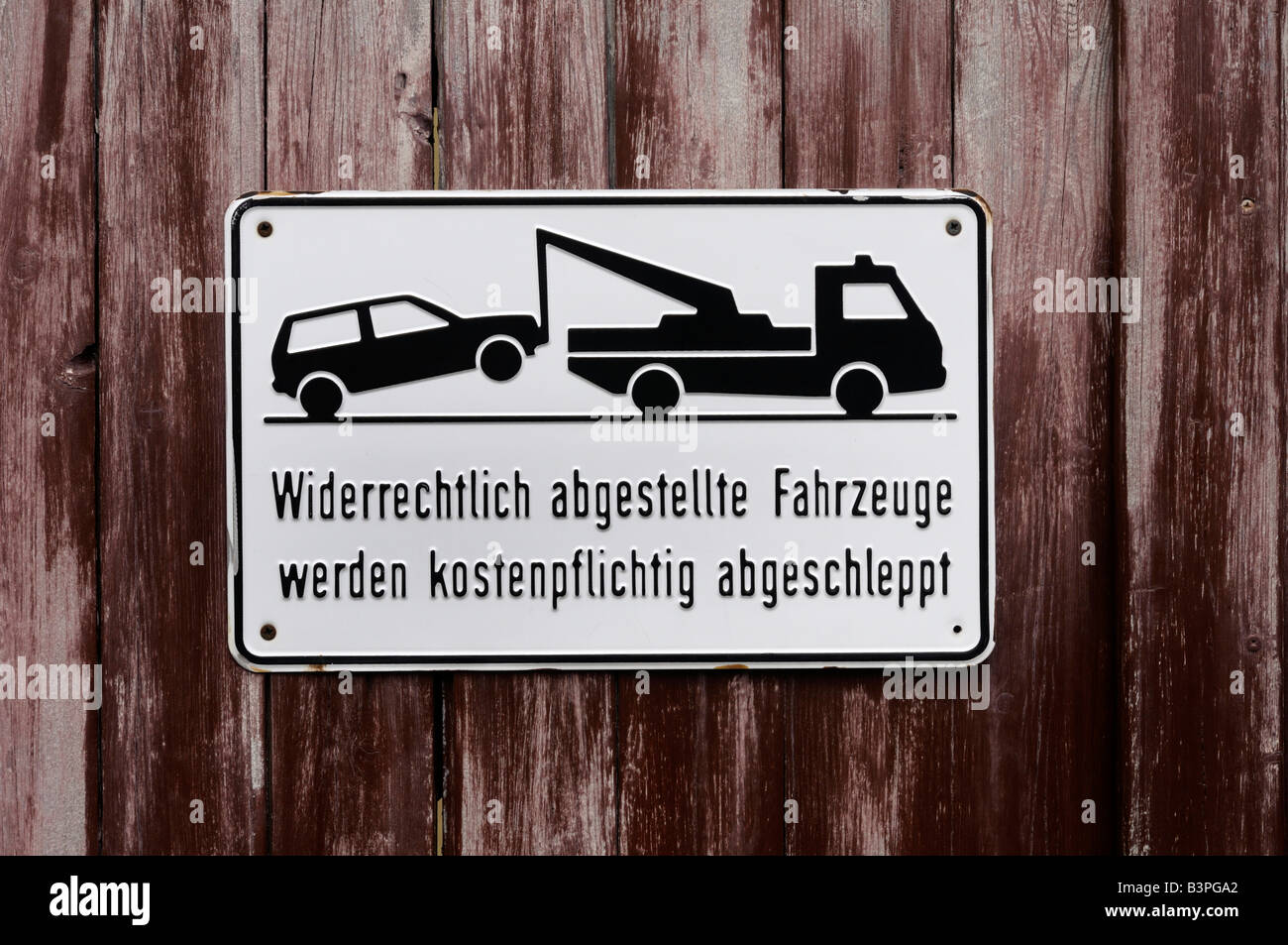 Sign on a wooden door, illegally parked vehicles will be towed away at the owners cost - Stock Image