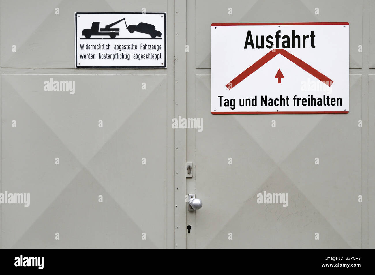 Garage door, grey metal garage door with signs, keep free day and night, illegally parked vehicles will be towed - Stock Image