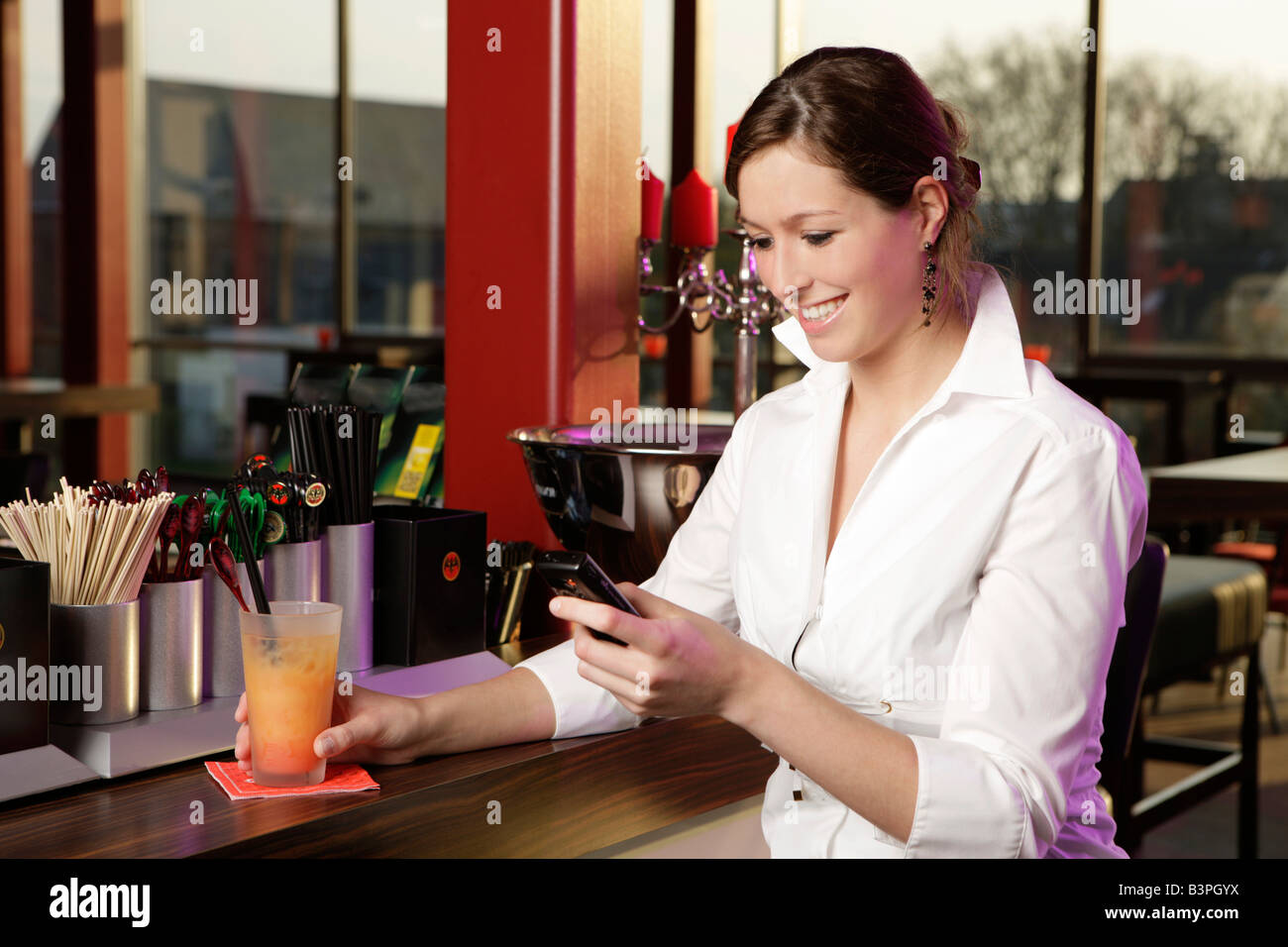 Young woman in a cafe bar looking at her cell phone - Stock Image