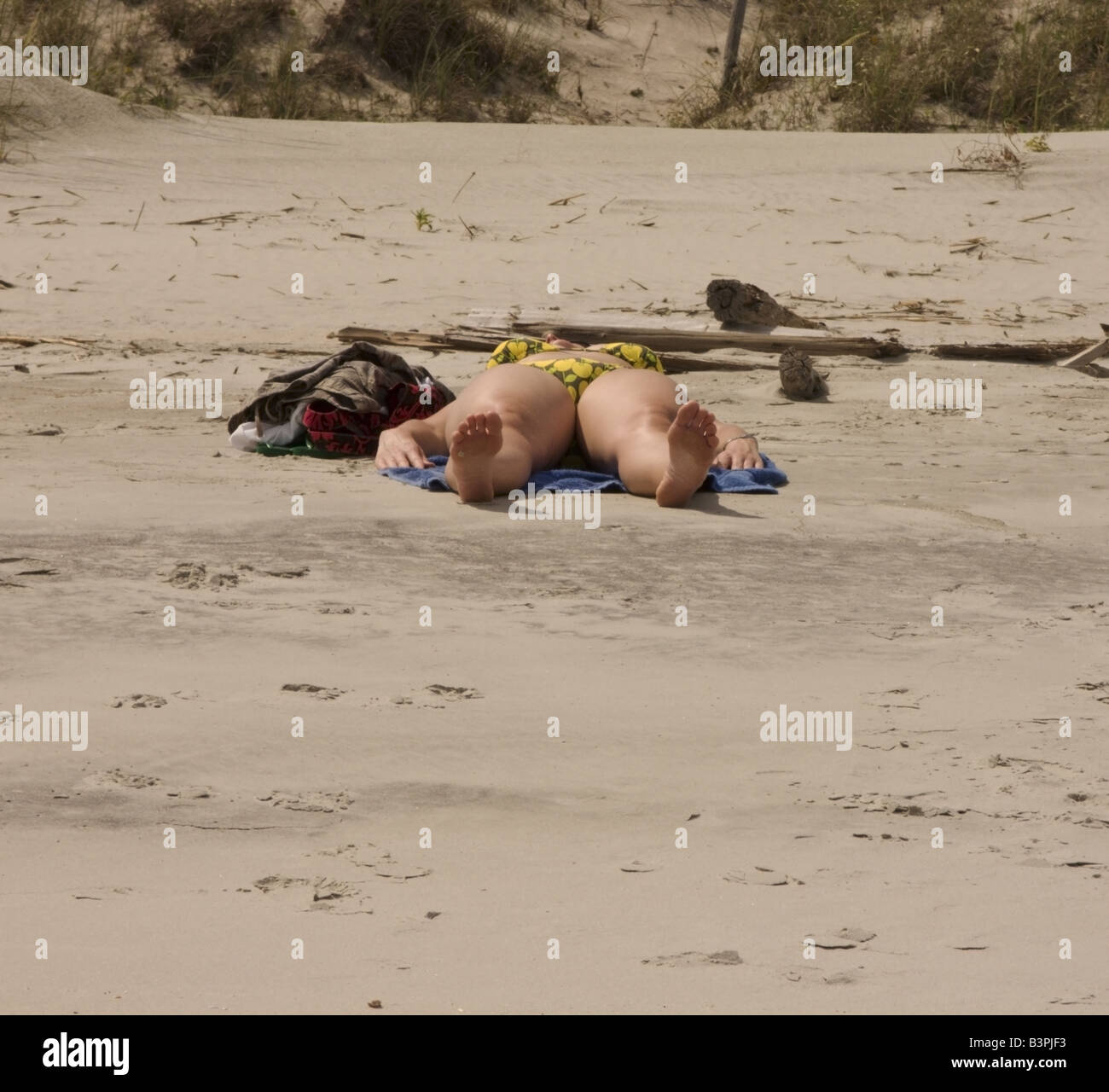 An obese sunbather lies on a beach near Myrtle Beach, South Carolina. - Stock Image
