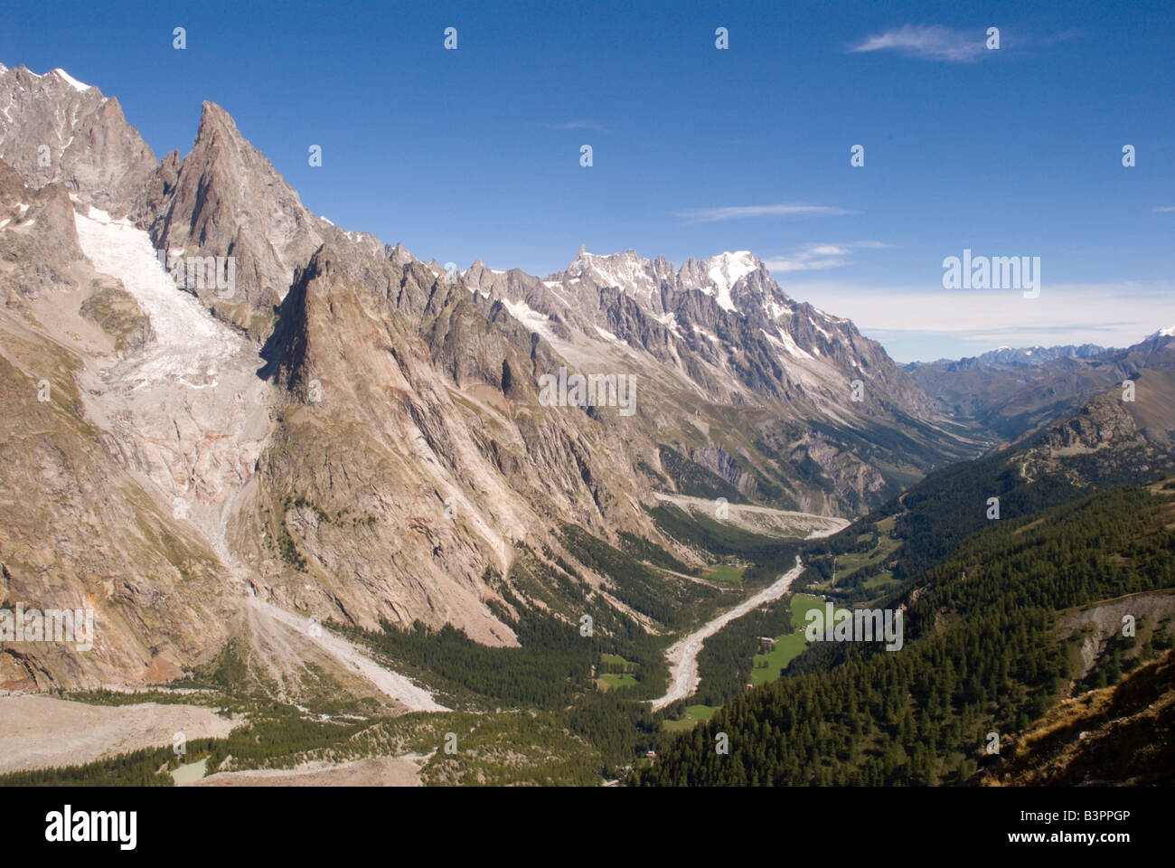 The green Val Veny runs beside the bare rock and ice of the Mont Blanc Massif. - Stock Image