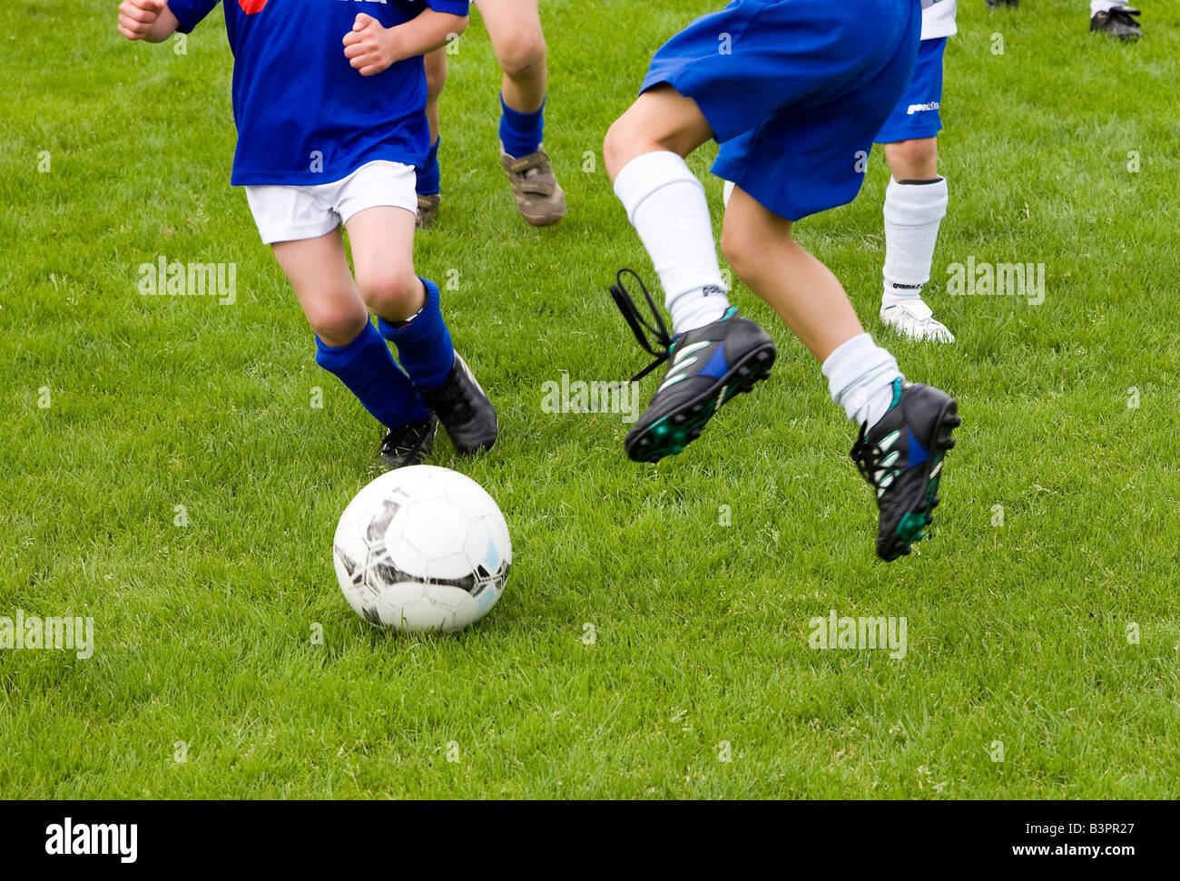 Close-up of players fighting for the ball in a soccer game for children - Stock Image