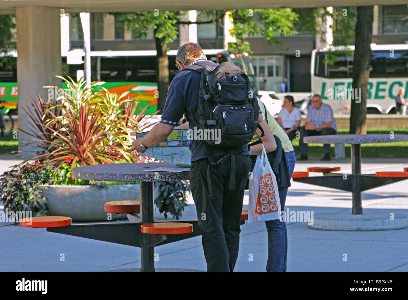 Tourists checking map in Nathan Phillips Square near Queen Street West in Toronto - Stock Image