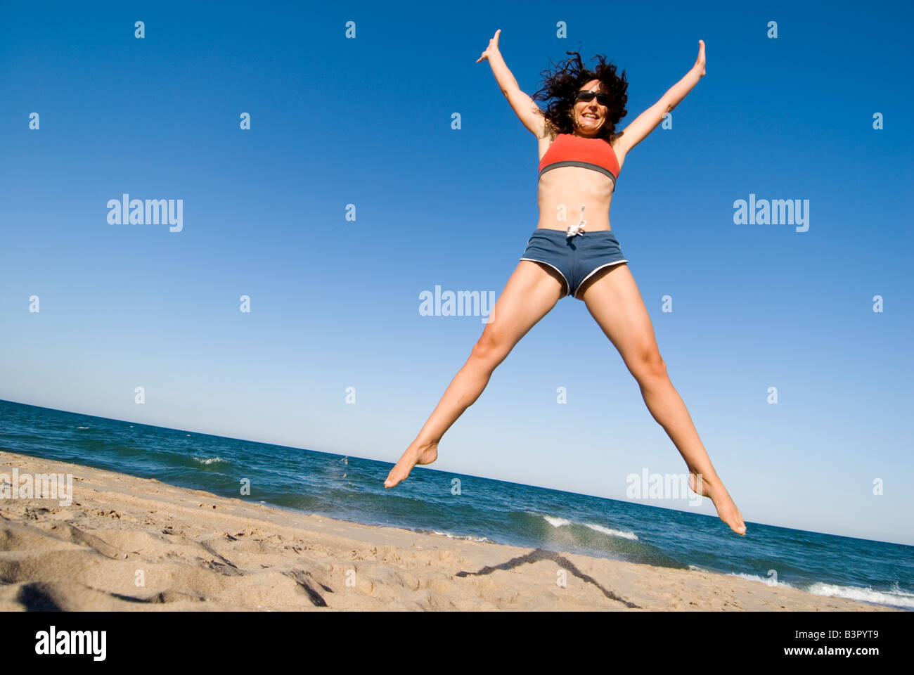 Model Released young woman doing star jump on a sandy beach against a clear blue sky. El Saler. Valencia Spain - Stock Image