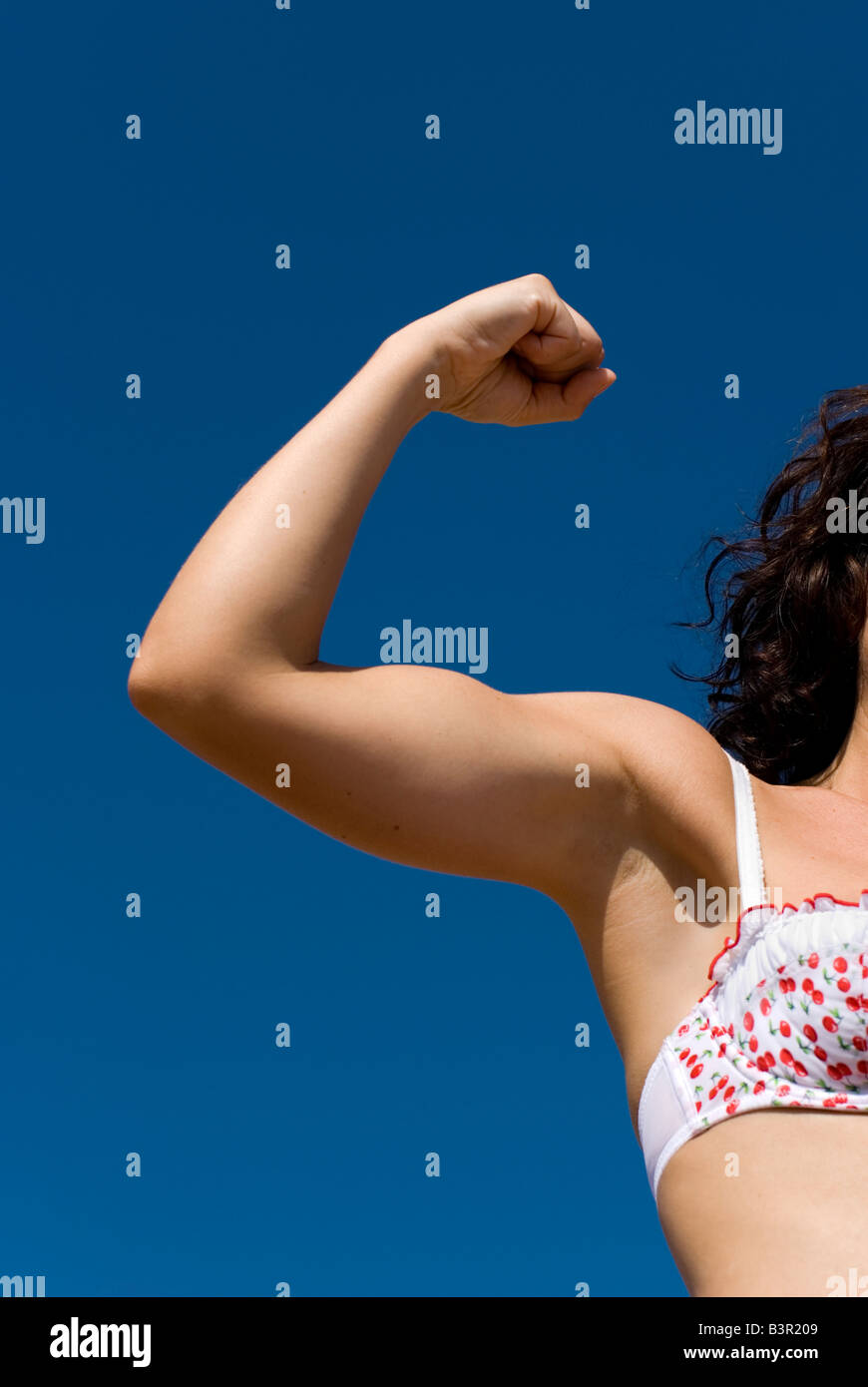 Model Released female arm flexing biceps against a clear blue sky wearing feminine floral bra - Stock Image