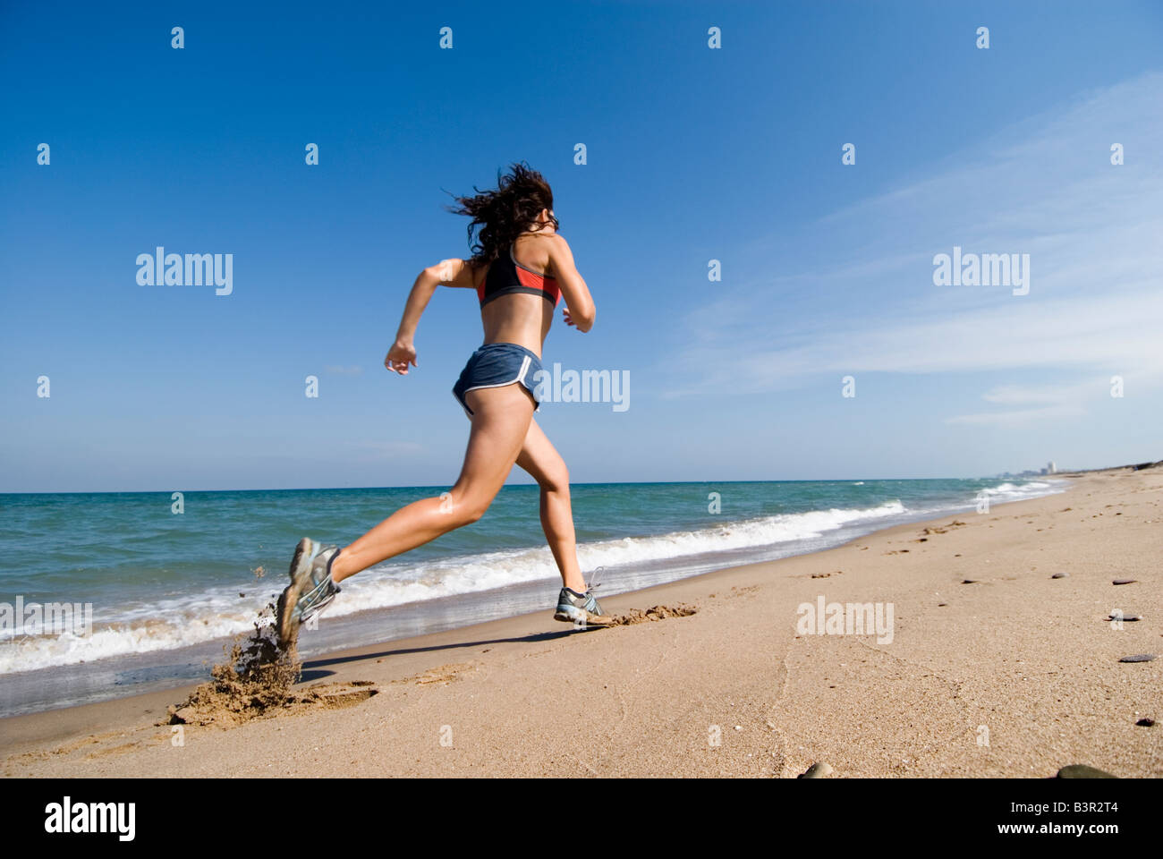 Model Released fit young woman running along shoreline of an empty sandy beach - Stock Image