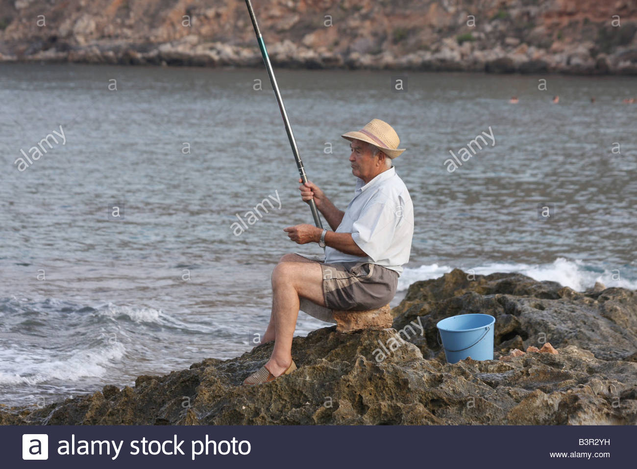 An old man fishing in the mediterranean sea on the spanish for Fishing rod in spanish