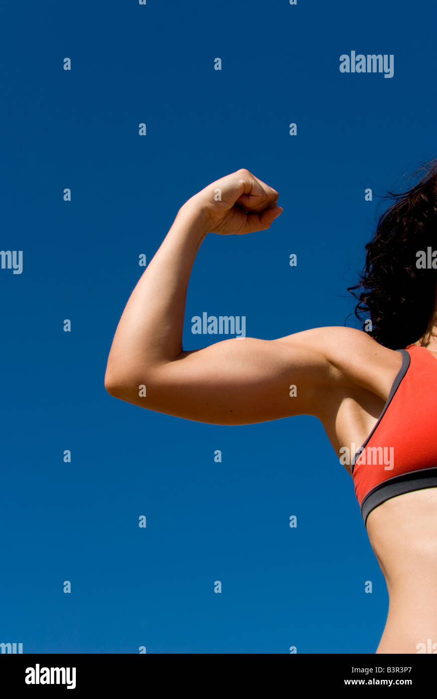 Model Released sporty female arm flexing biceps against a clear blue sky - Stock Image