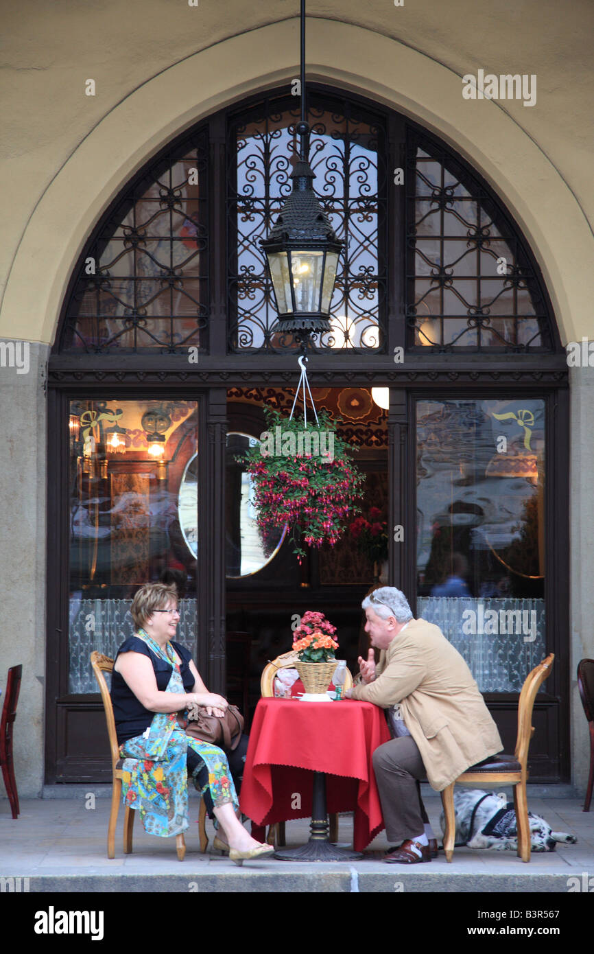A couple have drinks at the Cafe Noworolski's outdoor seating area beneath the Cloth Hall's arches,Market - Stock Image
