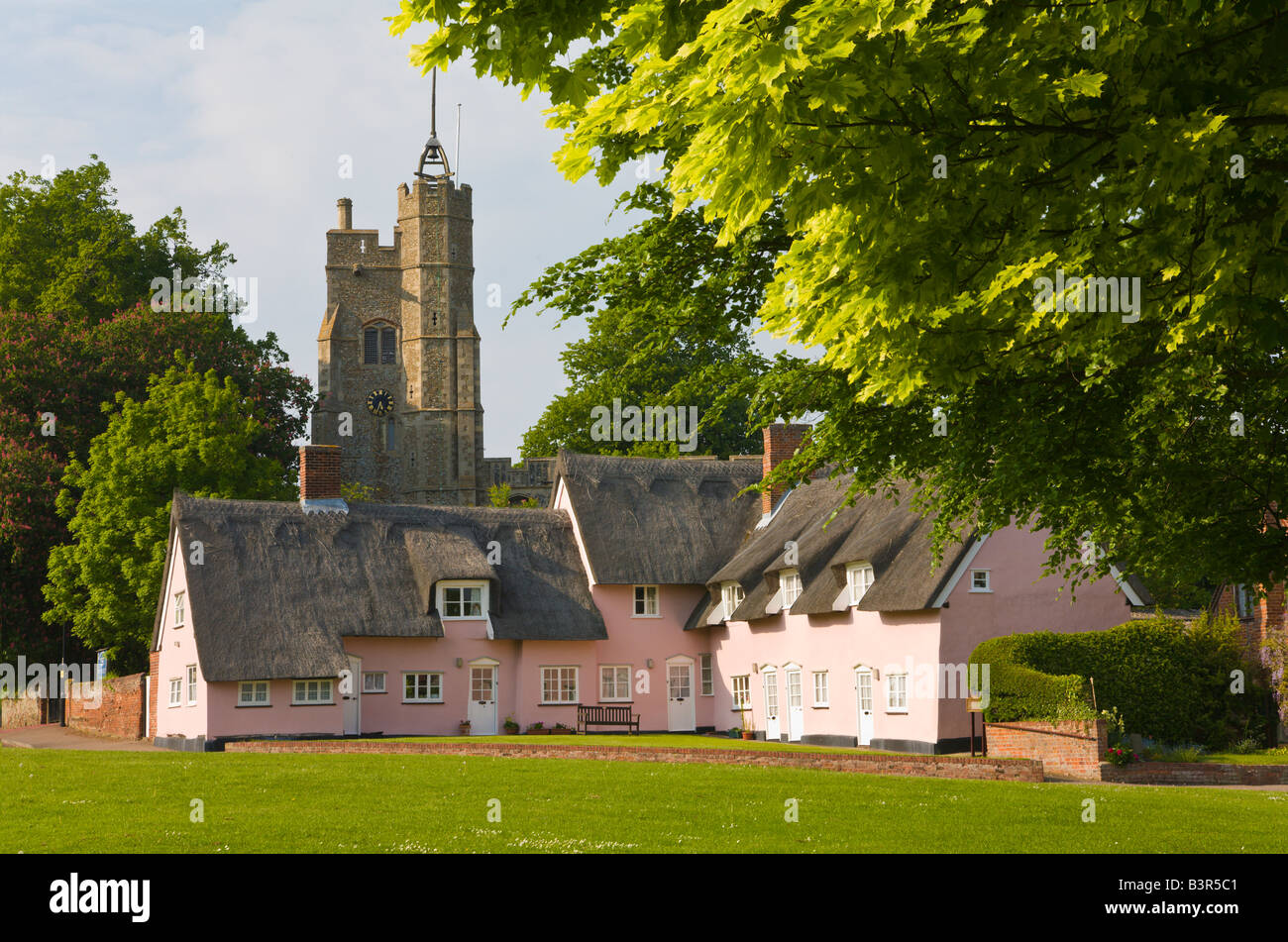 Church and thatched pink cottages, Cavendish, Suffolk, England - Stock Image