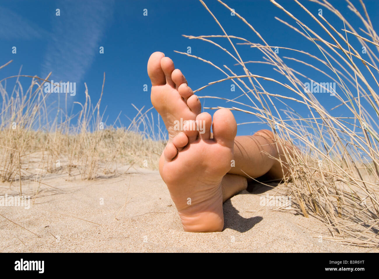 Model Released female feet lying in sand dunes with blue sky - Stock Image