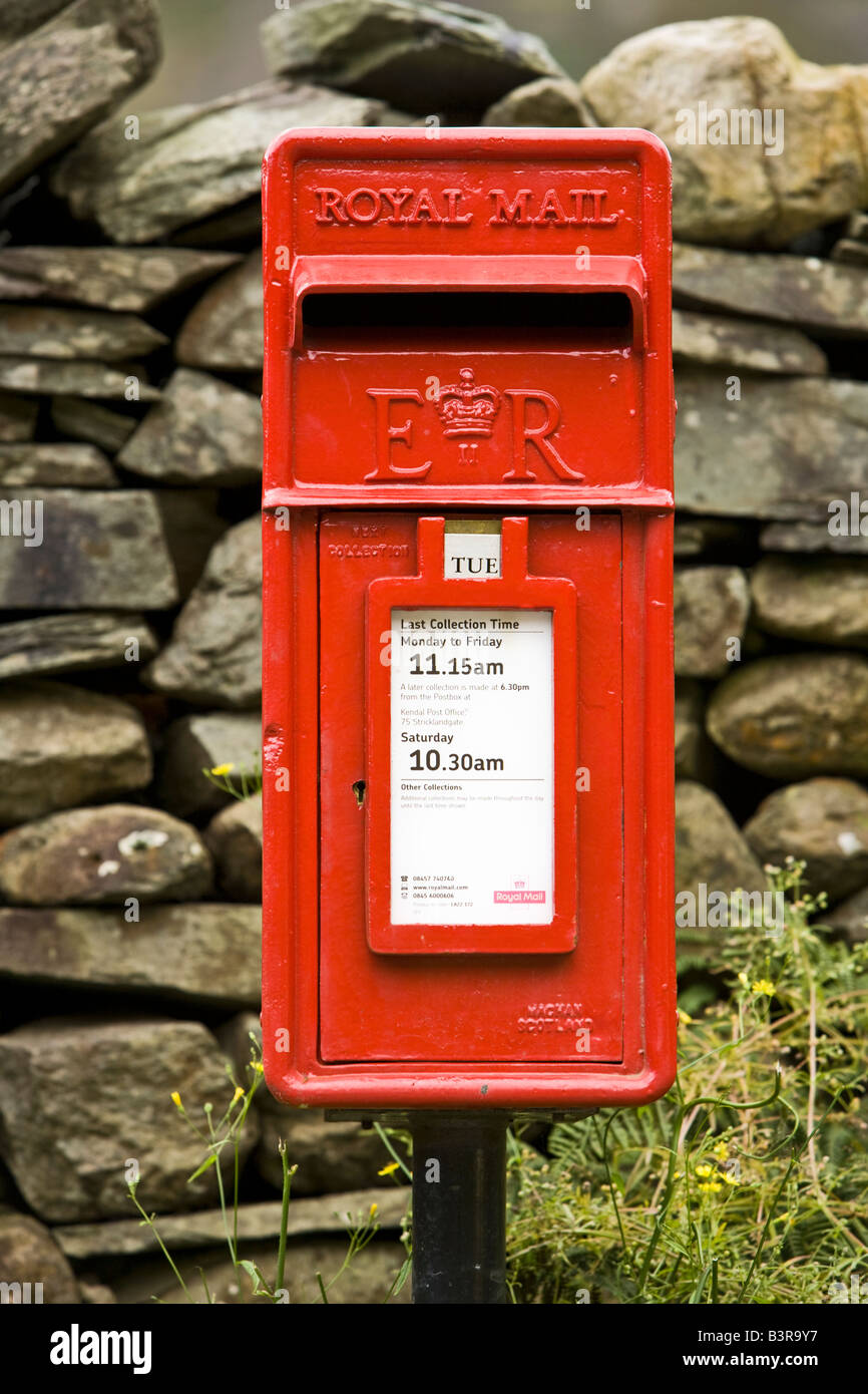 Traditional red Royal Mail post letter box and dry stone wall in rural England UK - Stock Image