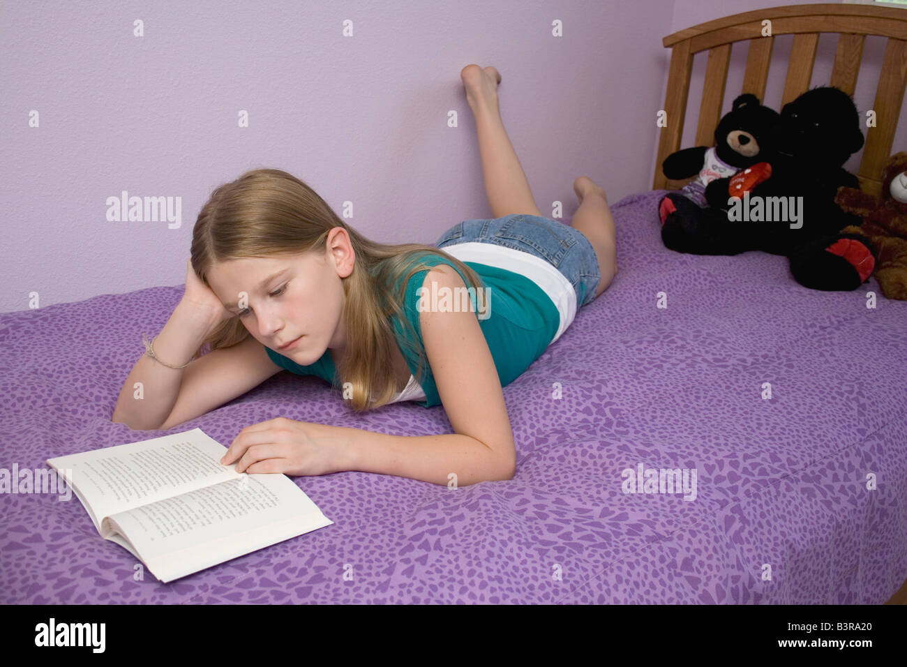 Young girl lying on bed on her stomach reading a book for In bed pics