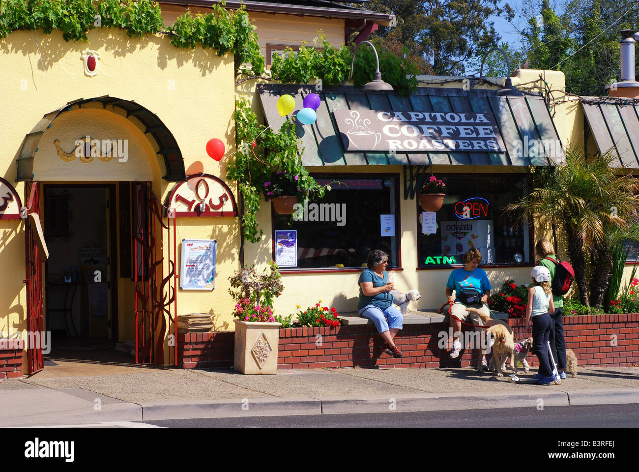 Two women sitting outside Capitola Coffee Roasters with their dogs visiting a woman and her daughter - Stock Image
