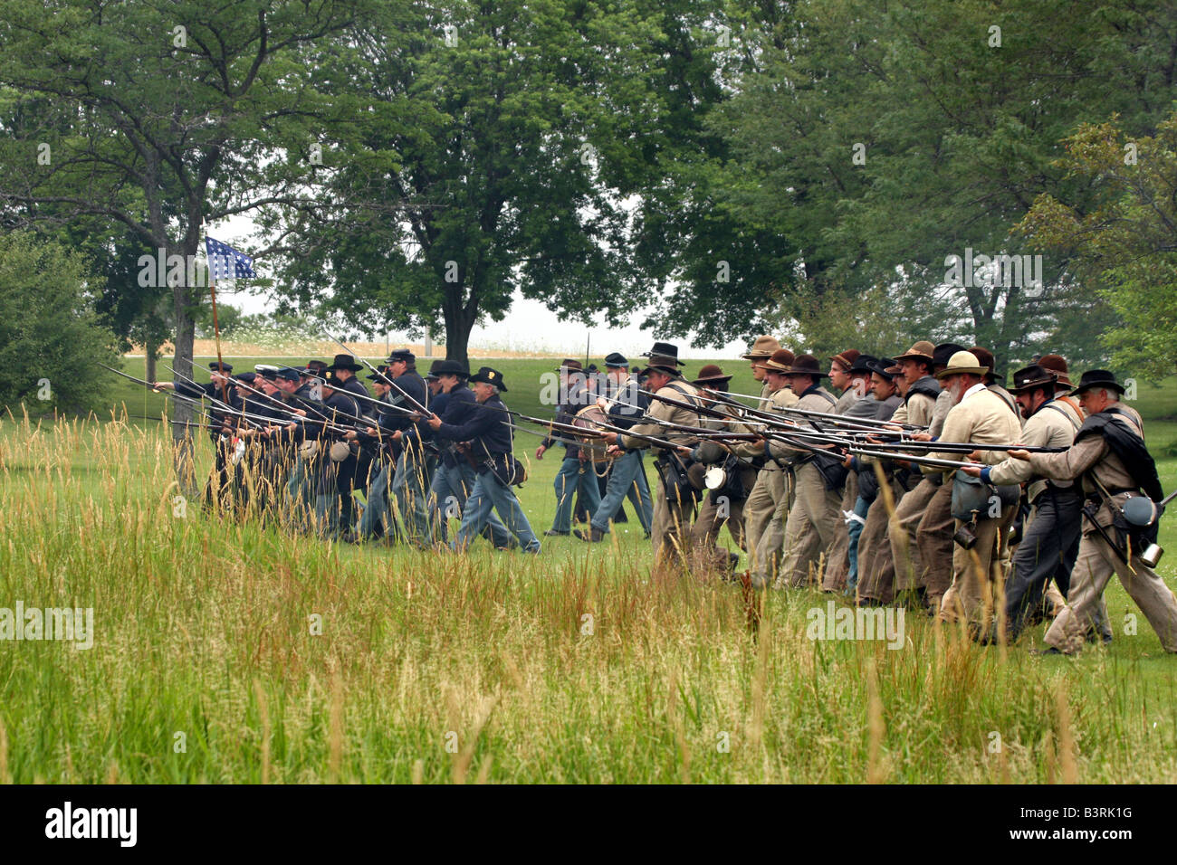Confederate and Union Soldiers advancing towards the crowd at a Civil War Encampment Reenactment Stock Photo