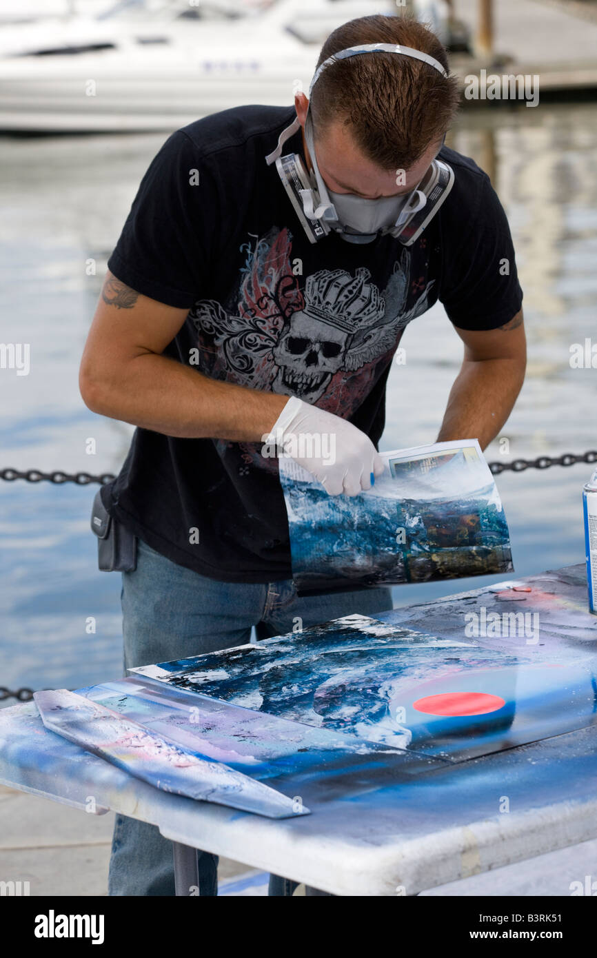 spray paint artist at work on harbourfront, Victoria, Vancouver Island, British Columbia, Canada - Stock Image