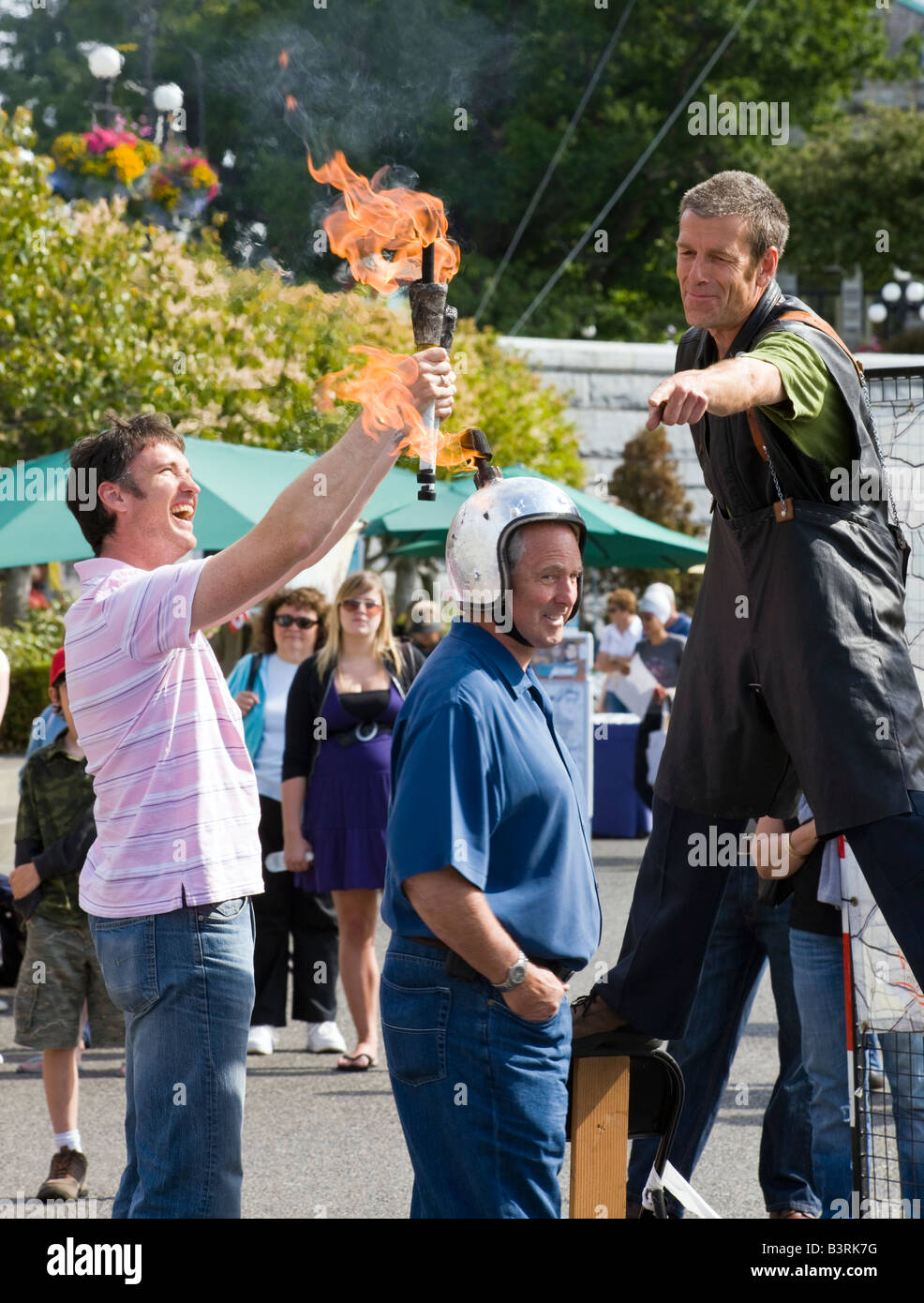 pavement artist on stilts with fire sticks at harbourfront, Victoria, Vancouver Island, British Columbia, Canada - Stock Image