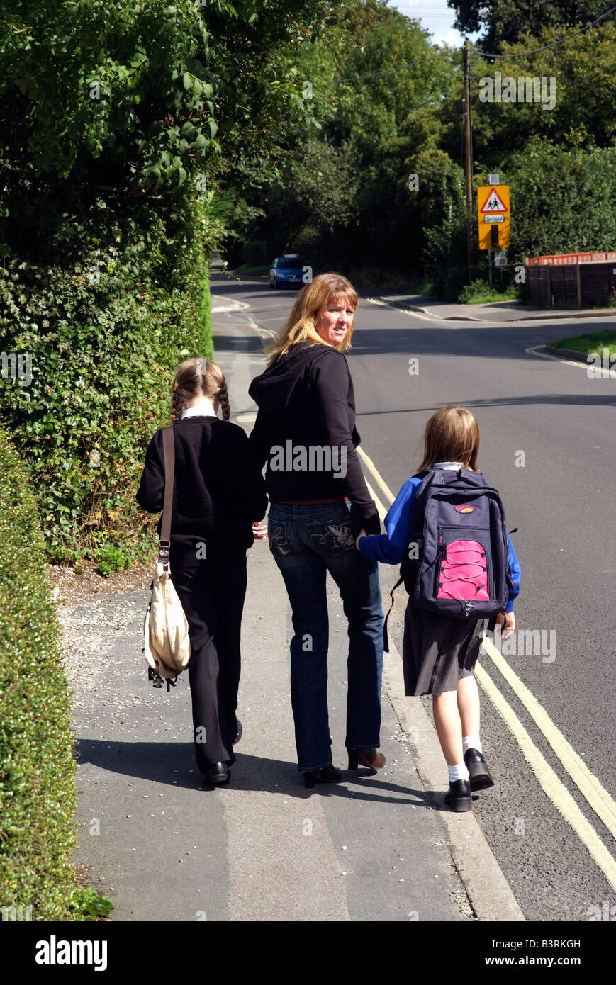 Mother and children walking to school along a pavement - Stock Image