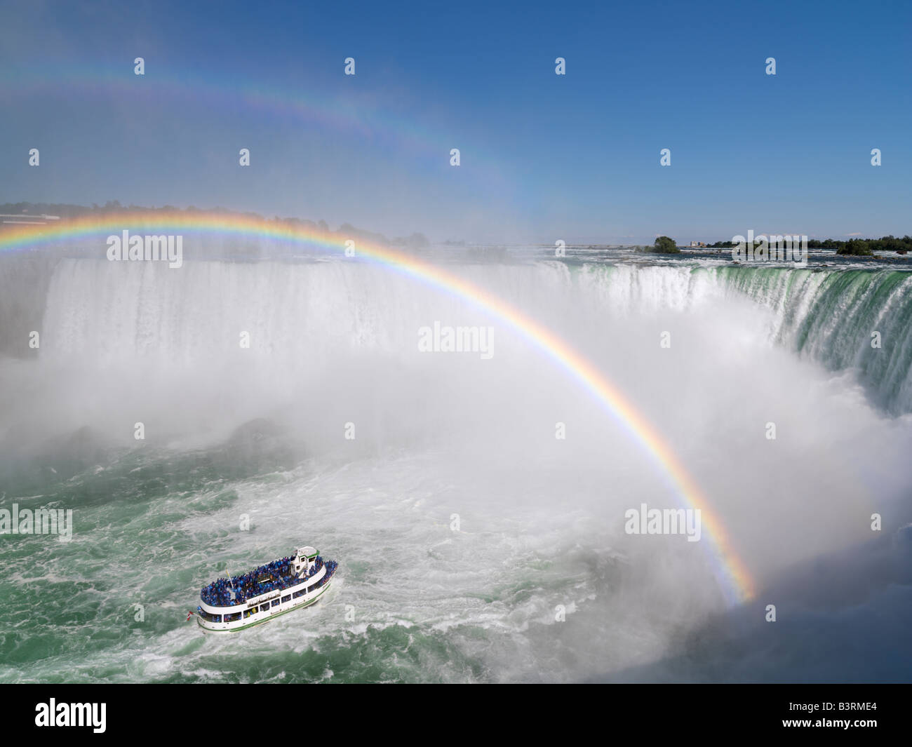 Canada,Ontario,Niagara Falls,Maid of the Mist tour boat approaching the Canadian Falls with a double rainbow - Stock Image