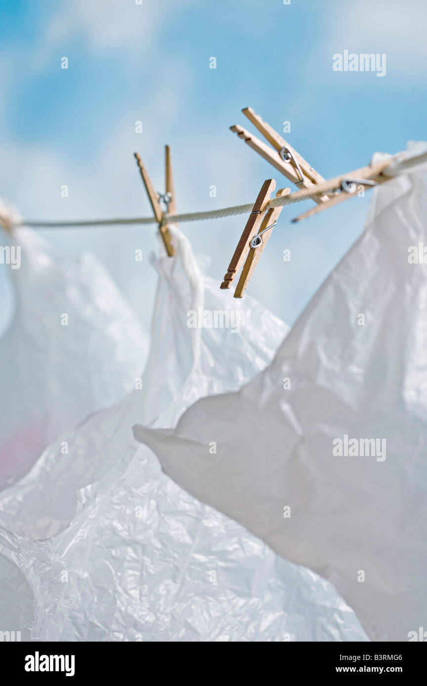 plastic bags hanging on laundry clothes line to dry and be reused - Stock Image