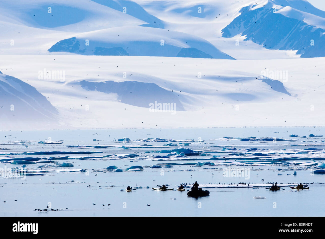 Kayakers by ice berg off coast of Nunavut, Canada - Stock Image