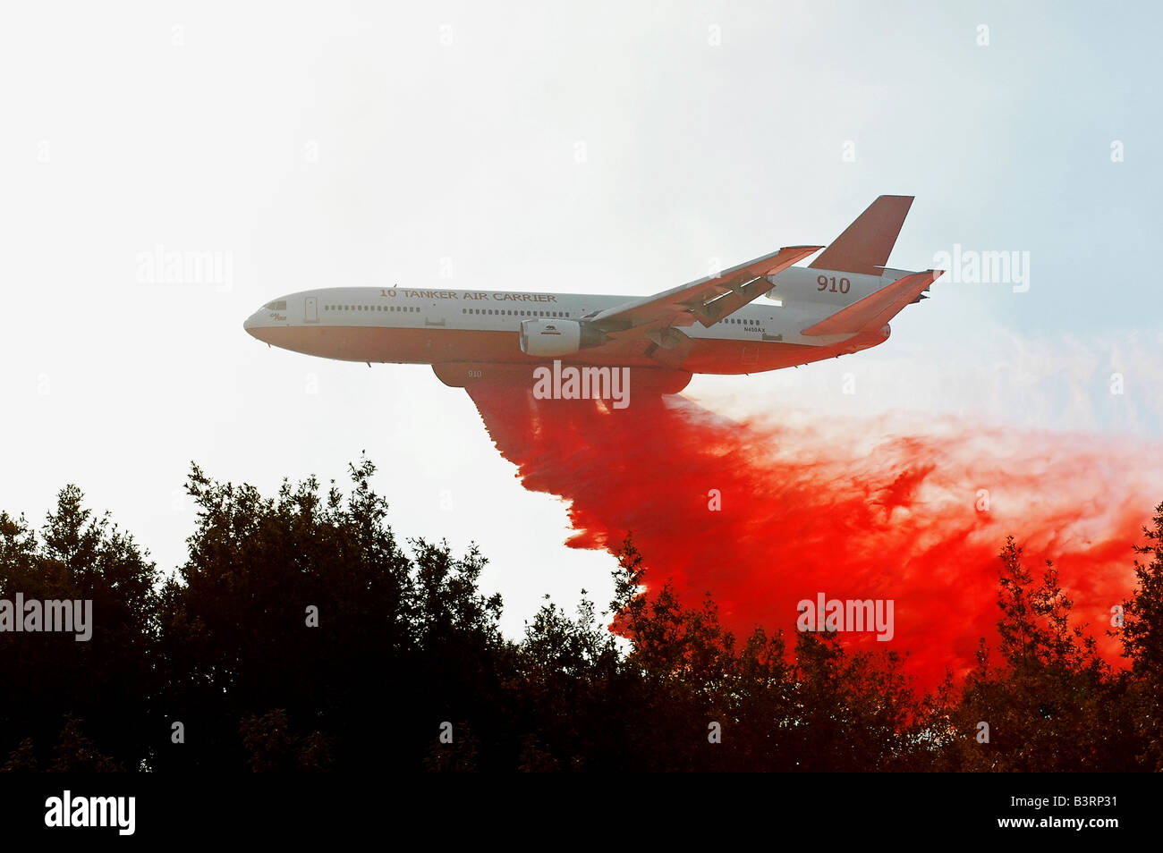 A firefighting DC 10 delivers a load of fire retardant onto a forest fire in California - Stock Image