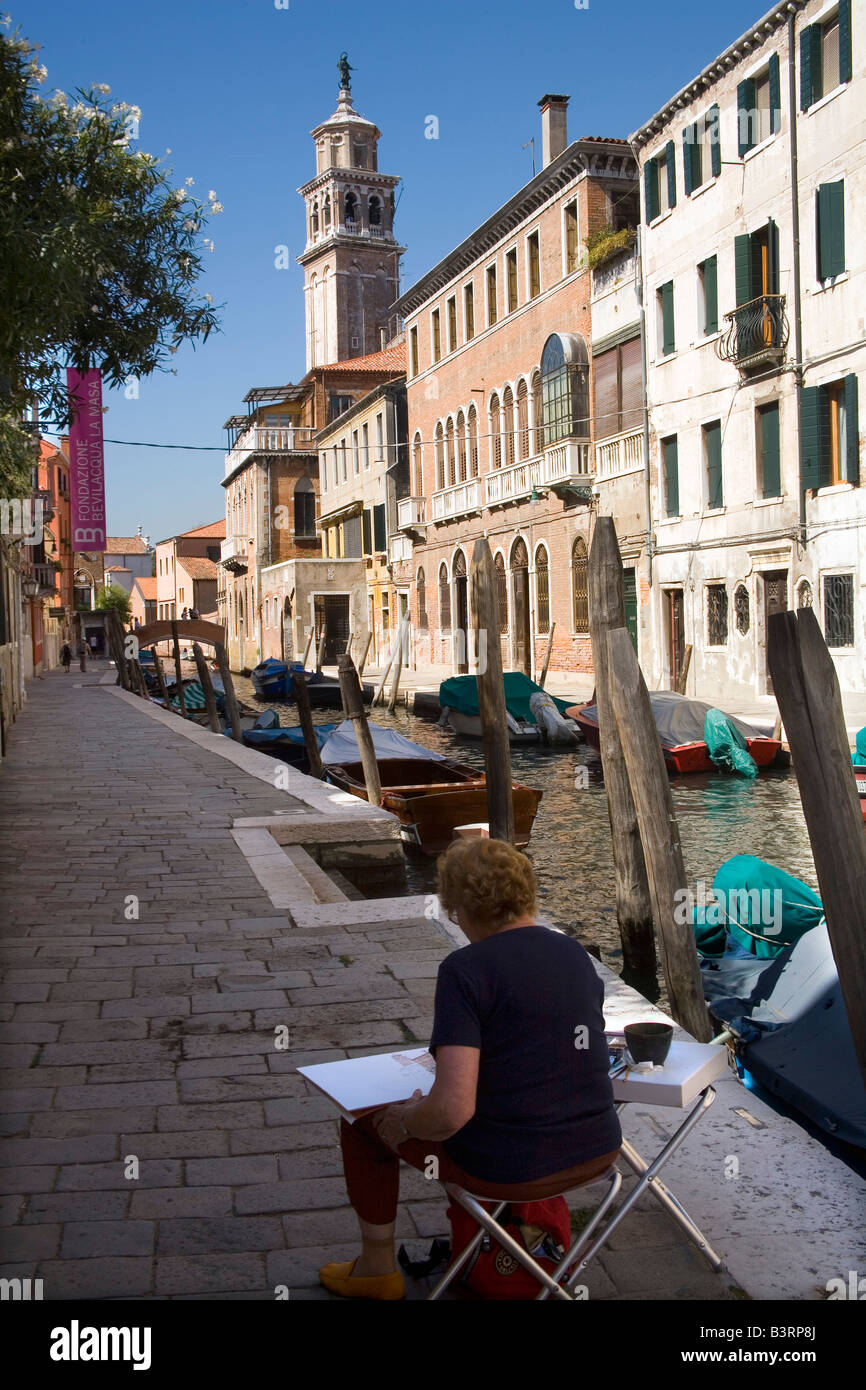Artist paints a watercolour of a quiet and pretty image of canal in Venice Italy - Stock Image