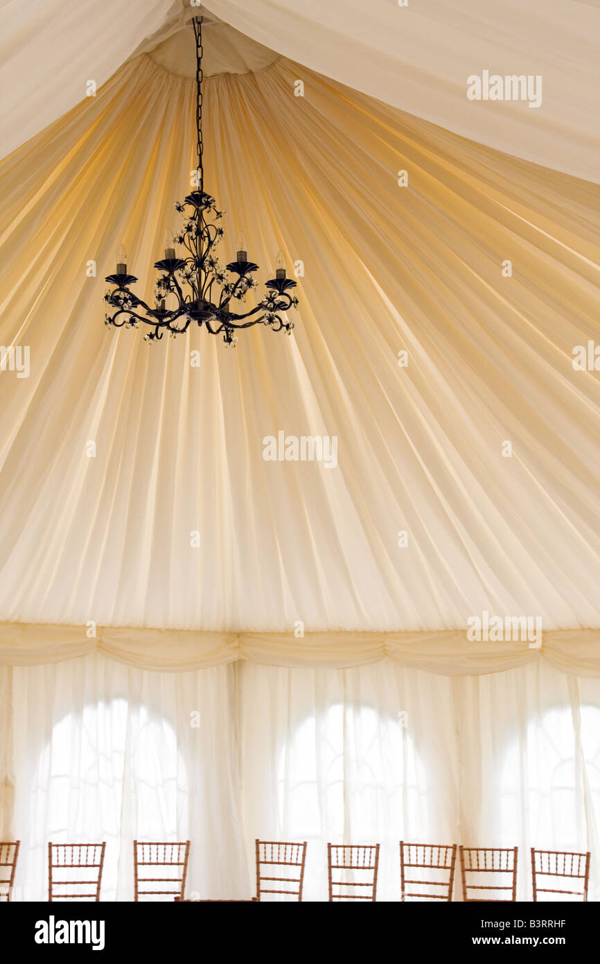 The interior of a wedding marquee with an unlit chandelier highlighting the folds of the fabric - Stock Image