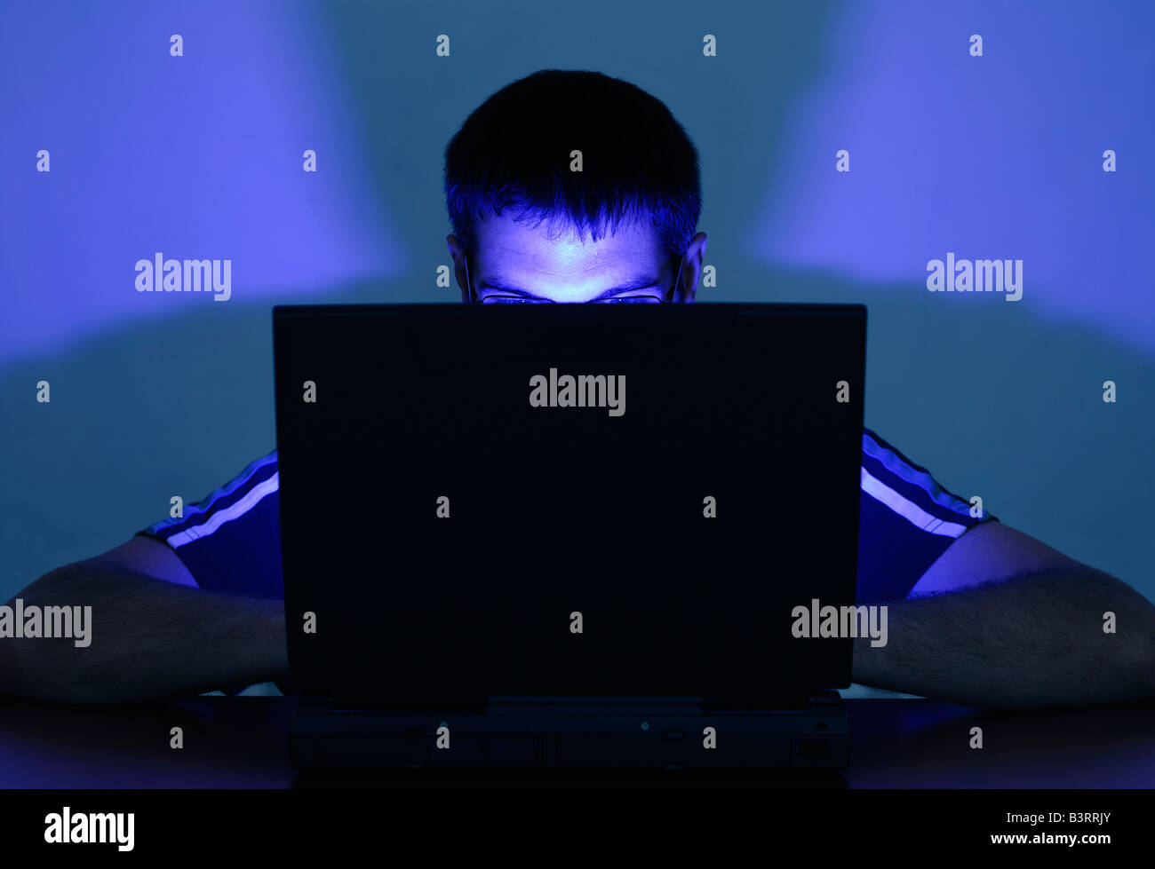 Man Using a Laptop with His Face Illuminated by the Screen Stock Photo