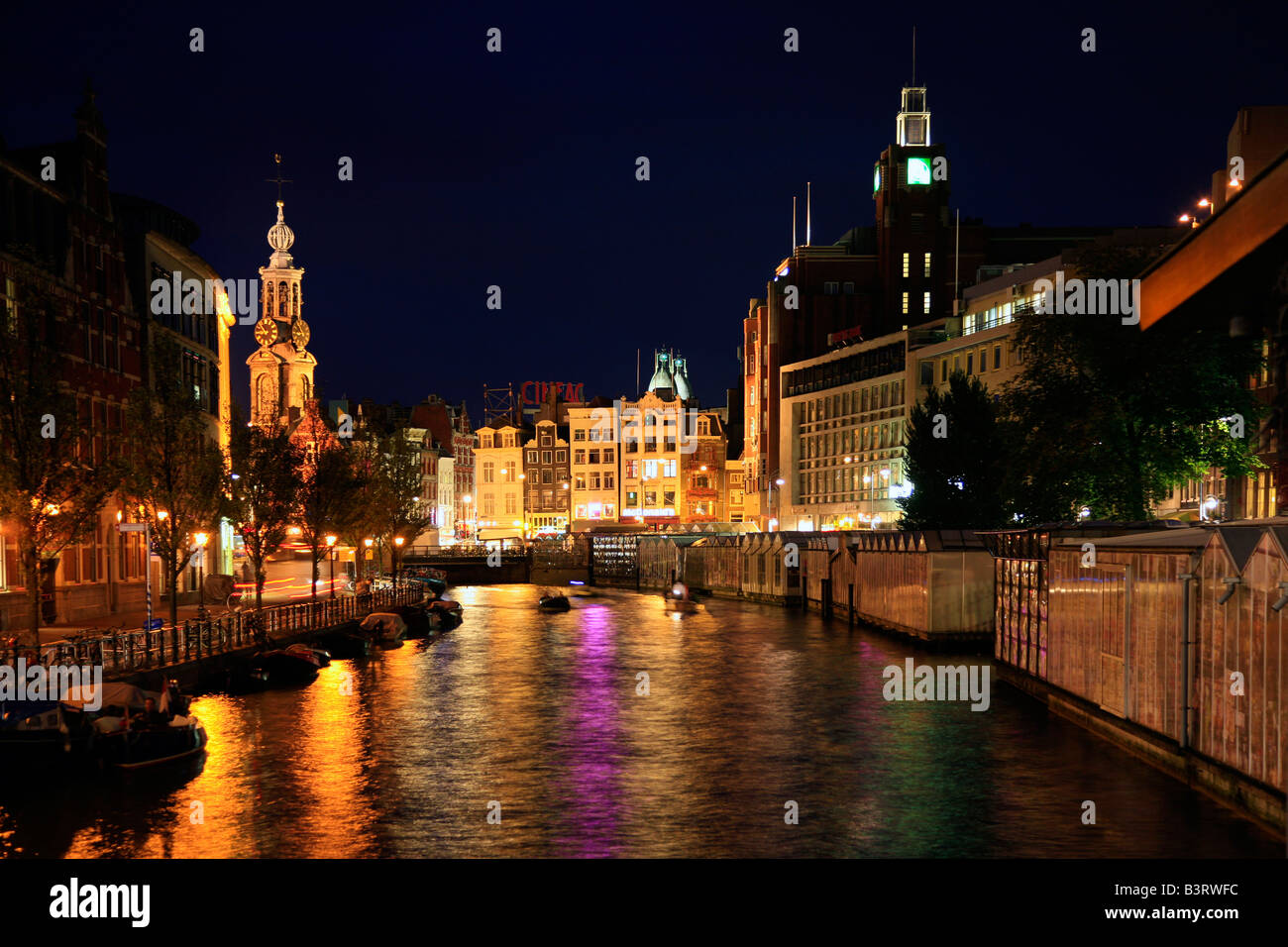 Amsterdam Singel canal at beautiful calm night with boats and colourful lighting with reflections,  the Netherlands Stock Photo