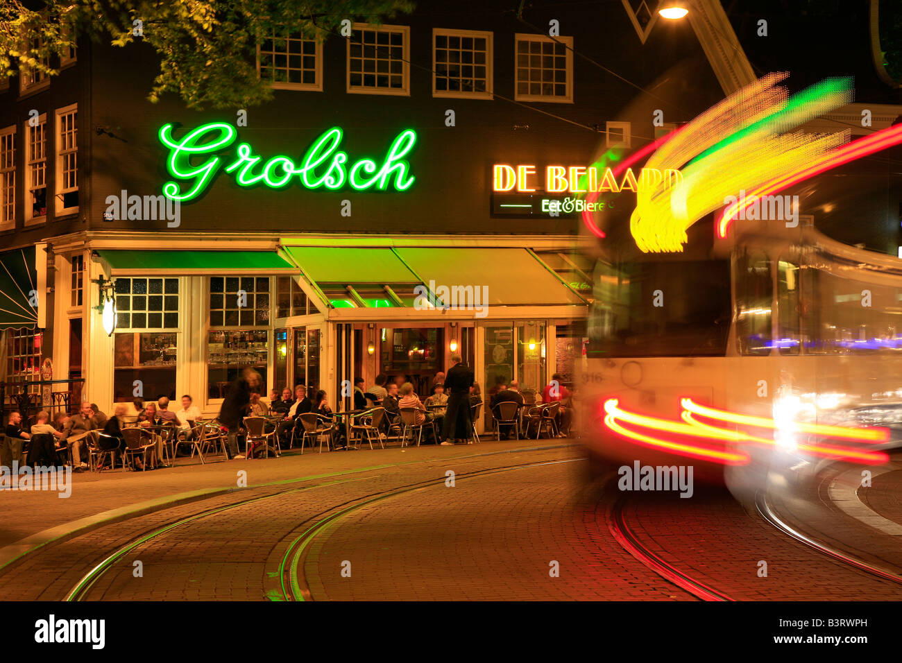 Amsterdam night scene: De Beiaard pub with Grolsch neon sign and moving tram creating traces of colourful lights - Stock Image