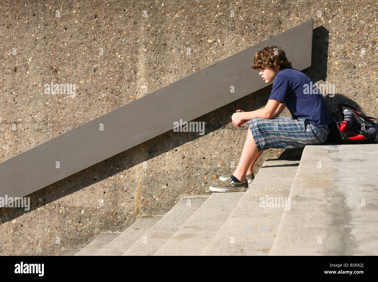 A Pre Adolescent Young Boy Sits At The Top Of Cement Stairs Hunched