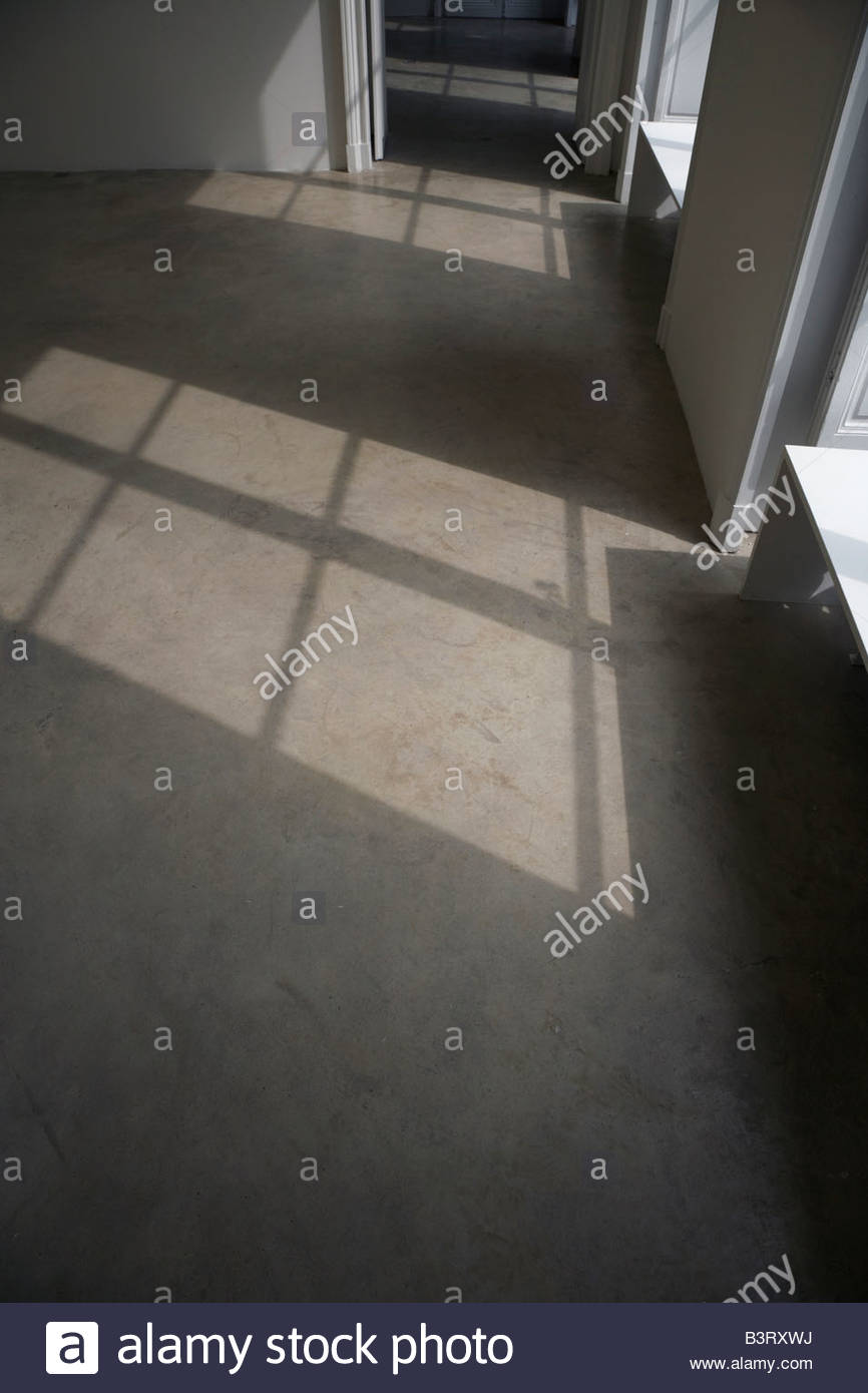 sunlight shining through a window on to a smooth concrete floor - Stock Image