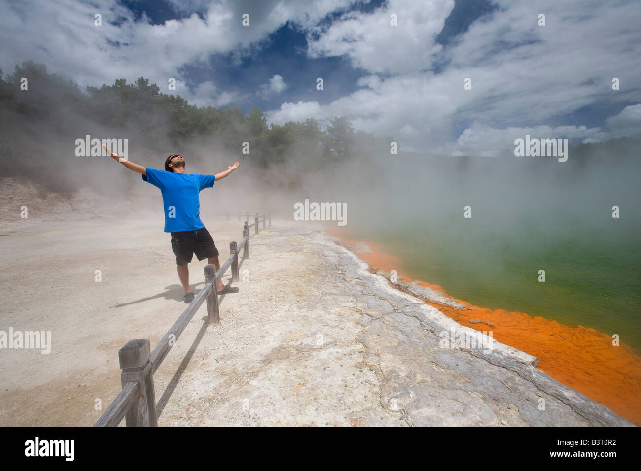 Man at Champagne Pool at geothermal site, Wai-O-Tapu Thermal Wonderland on North Island of New Zealand - Stock Image