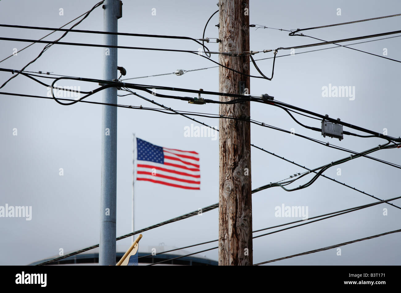 American flag behind phone wires and electrical wires - Stock Image
