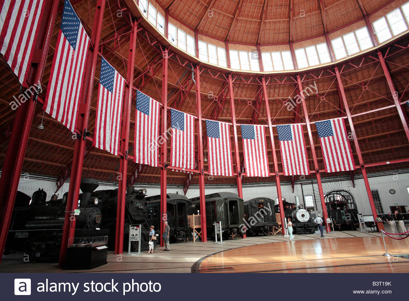 Locomotives and US flags in the roundhouse at the Baltimore and Ohio Railroad Museum in Baltimore Maryland - Stock Image