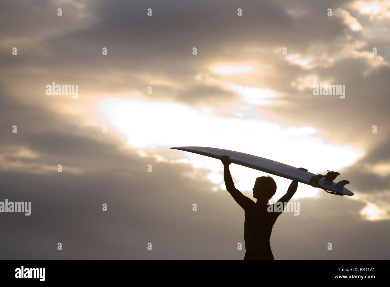 A surfer on Muriwai Beach, New Zealand - Stock Image
