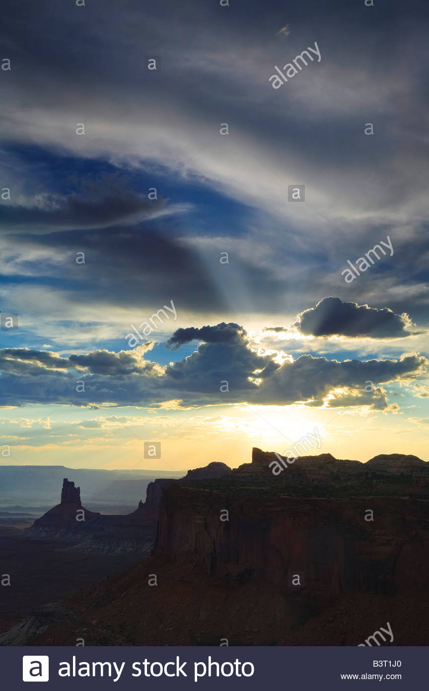 The sun shines through a hole in the clouds forming crepuscular rays over Canyonlands National Park, Utah. - Stock Image