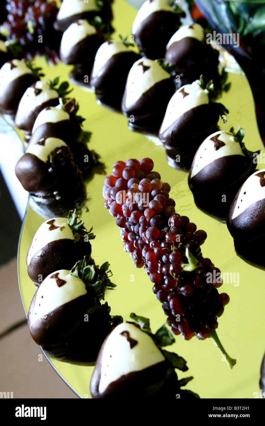 Strawberries decorated to look like tuxedos - Stock Image